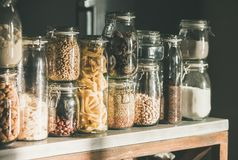 Rustic kitchen food storage arrangement over kitchen counter. Rustic kitchen food storage arrangement. Grains, cereals, nut, dry fruit, flour, pasta kinds in royalty free stock photo