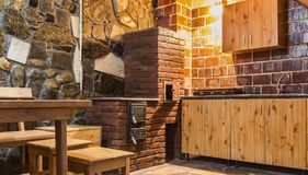 Rustic Kitchen. With wooden furniture and brick oven in a chalet Stock Image
