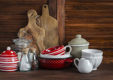 Rustic kitchen still life. Olive cutting board,  jar of flour,  bowls, pan, enamelled  jar,  gravy boat. On a dark brown wooden ta Stock Image