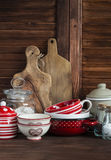 Rustic kitchen still life. Olive cutting board,  jar of flour,  bowls, pan, enamelled  jar,  gravy boat. On a dark brown wooden ta Royalty Free Stock Image