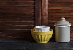 Rustic kitchen still life. vintage ceramic bowl and enameled jar. On dark wooden table Stock Image
