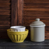 Rustic kitchen still life. vintage ceramic bowl and enameled jar. On dark wooden table Royalty Free Stock Images