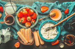 Rustic kitchen table with strawberry tiramisu cooking ingredients, top view. Stock Photography