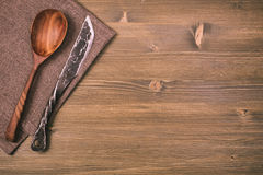 Rustic knife and spoon on wooden background Stock Images