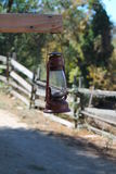 Rustic lantern on country road. Metallic lantern hanging off wooden plank in apple orchard Stock Photography