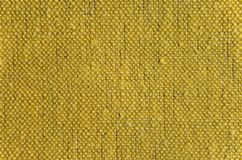 Rustic linen fabric background. Texture of rustic linen fabric of yellow color royalty free stock images