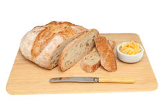 Rustic loaf on bread board Stock Photos