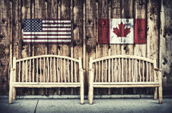 Rustic Log Benches with USA and Canada flag. Two rustic wooden log benches sit side by side outdoor against a building wall made of wooden siding with a USA and Royalty Free Stock Photo