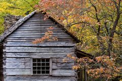 Rustic Log cabin on a fall day. Rustic grey Log cabin with hand hewn logs, dovetail joints and stacked stone chimney on a fall day with colorful foliage royalty free stock photography