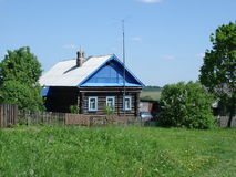 Rustic log cabin. Old log house in the village Ryuminskoe Vladimir Oblast, Russia, rustic farm on sunny summer day against a bright blue sky, lilac bush in front Royalty Free Stock Photo