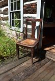 Sunlit antique chair on the porch of a log cabin. Rustic log cabin on a sunny,summer day Royalty Free Stock Photos