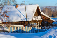 Rustic log house covered with snow. Village Visim, Sverdlovsk region, Russia. Rustic log house covered with snow. Russian old-believer village Visim in the low Royalty Free Stock Photo