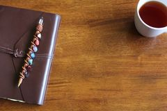 Rustic Leather Notebook with Pen and Cup of Tea royalty free stock photo