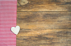 Rustic love background, wooden heart on red checkered fabric. Rustic wooden heart on red checkered fabric and brown wood with copy space Stock Photos