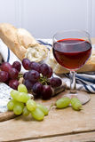 Rustic lunch. A glass of red wine with baguette and grapes in rustic still life Royalty Free Stock Image