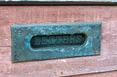 Rustic mailbox in door. Old rustic mailbox opening in red door Royalty Free Stock Images