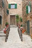 Rustic mediterranean village Valldemossa at Mallorca, Spain. Rustic mediterranean village with flowerpots, flowers, ancient architecture, stairs and shutters in Royalty Free Stock Photos