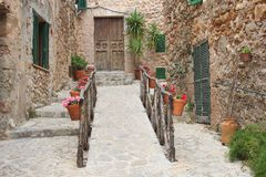 Rustic mediterranean village, Majorca, Spain. Rustic mediterranean village with flowerpots, flowers, ancient architecture, stairs and shutters in the village Royalty Free Stock Image