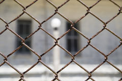 Rustic metal chain-link fence with a window and light pole Stock Image