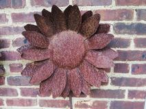 Rustic Metal Flower Against Brick Background. Rusty metal flower against a brick background royalty free stock photos