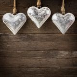 Rustic metal heart ornaments hanging on wood Royalty Free Stock Images