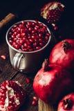 Rustic metal mug full of pomegranate seeds royalty free stock image