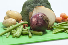 Rustic mixed veg. On a green chopping board Royalty Free Stock Photos