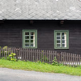 Rustic mountain cottage front in brown and green. Authentic rustic nd brown mountain cottage front with windows and stones in Orlicke Mountains, Czech republic Royalty Free Stock Photos