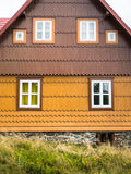 Rustic mountain cottage front in brown and yellow. Authentic rustic yellow and brown mountain cottage front with windows and stones in Bohemian Forrest, Czech Stock Photography