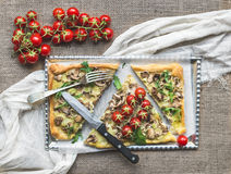 Rustic mushroom (fungi) square pizza with cherry tomatoes and ar. Ugula over a sackcloth background Royalty Free Stock Images