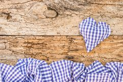 Rustic Oktoberfest background with heart and border in bavarian blue and white checked fabric stock photos