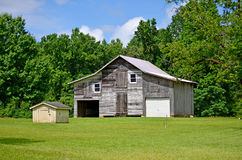 Rustic Old Barn Shed Garage and Pump House. Rustic old barn with one side turned into a garage sitting next to the edge of some woods in a grassy open lot with a Royalty Free Stock Photo