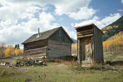 Rustic old cabin and outhouse in Fall Season Stock Photo