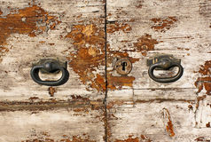 Rustic old door with knobs. Rustic olf shabby door with handles and lock Royalty Free Stock Photo