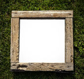 Rustic old grunge wood frame on grass, empty space for text. Royalty Free Stock Photos