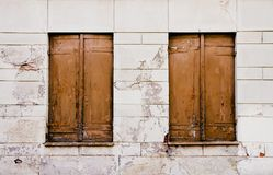 Rustic old grungy and weathered brown wooden closed windows shutters with peeling paint on a white cracked wall stock photo