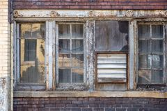 Rustic old industrial building windows with chicken wire. Chicken wire covering old abandoned factory building windows in inner city stock photography