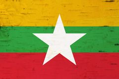 A rustic old Myanmar flag on weathered wood royalty free stock photo