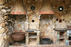 Rustic Old Outdoor Kitchen. Old pioneer style outdoor kitchen with iron and copper pots and stone and tile walls and counters Stock Image
