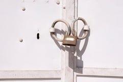 Rustic old padlock on white metal door Royalty Free Stock Images