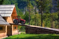 Rustic old red tractor on ramp of wooden barn Stock Photos