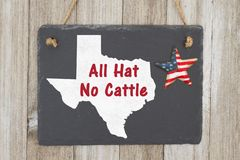 A rustic old Texan saying. A retro chalkboard with a vintage USA star hanging on weathered wood background with text All Hat No Cattle stock photo