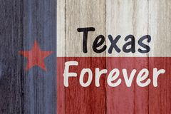 A rustic old Texas Forever message. Texas flag on weathered wood background with text Text Forever stock image