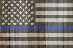 A rustic old thin blue line flag on weathered wood. For a background stock photography