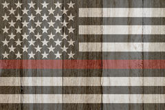A rustic old thin red line flag on weathered wood. For a background royalty free stock images