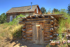 Rustic Old Time Log Cabin And Root Cellar. Rough-hewn root cellar built into the hillside next to an authentic log cabin circa 1800s stock image