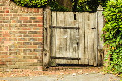Rustic old wooden gate in brick wall Stock Photo