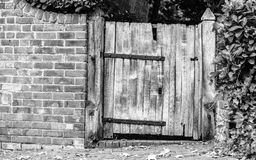 Rustic old wooden gate in brick wall Stock Photos