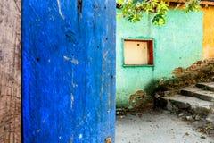 Rustic open blue door & turquoise & yellow wall stock image