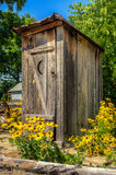 Rustic Outhouse with Flowers Stock Photos